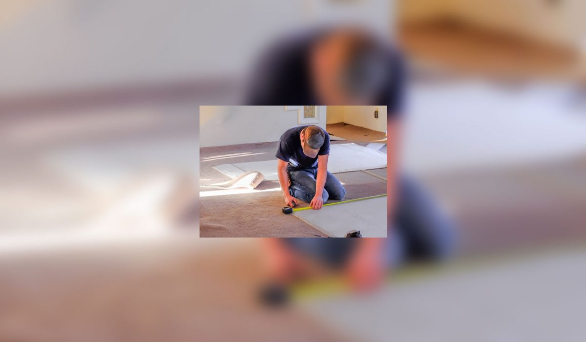 A man is measuring the the floor to make a carpet.